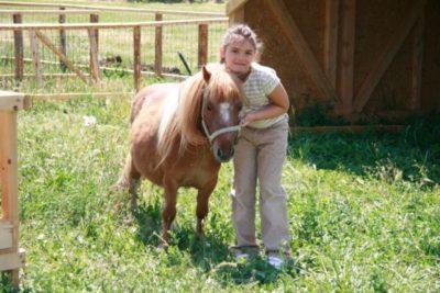 Fetiță fericită lângă ponei
